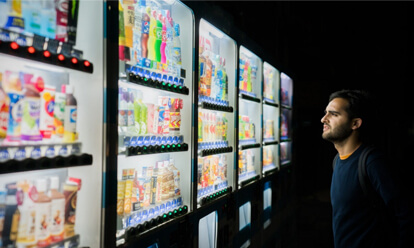 Man looking at vending machine trying to choose a drink